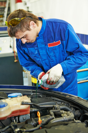 antifreeze: auto repairman mechanic worker changing antifreeze in car auto repair or maintenance shop service station