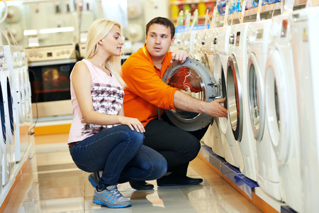 Young man choosing washing machine in home appliance shopping mall supermarket Stock Photo