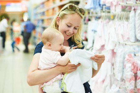 mum: woman choosing children apparel with little baby child girl on hands in clothing shop supermarket