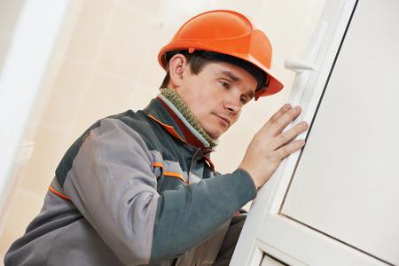 deadbolt: Male worker handyman carpenter at lock installation into wood door