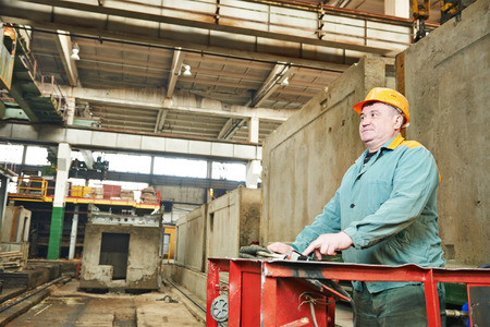 housebuilding: industrial worker at house-building plant factory workshop