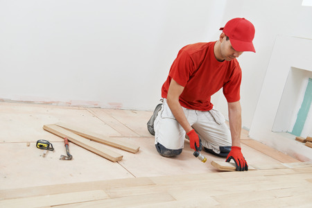 carpenter worker installing wood parquet board during flooring work with hammer Stockfoto
