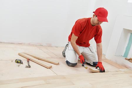 carpintero: trabajador carpintero instalar a bordo de parquet de madera durante suelos trabajo con martillo