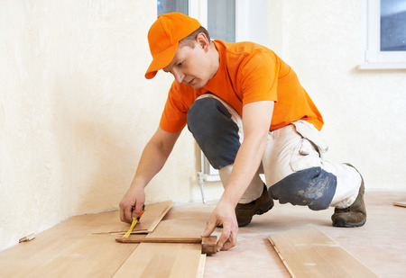 parquet floor layer: carpenter worker measuring wood parquet board during flooring work with hammer Stock Photo