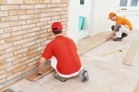 tongue and groove: Two parquet carpenter workers installing wood board during flooring work Stock Photo