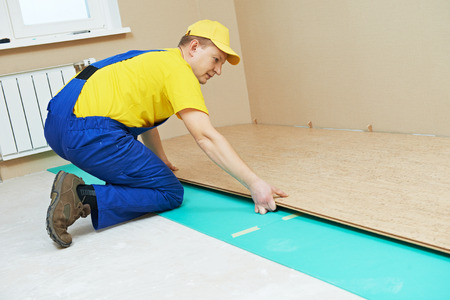 One carpenter worker laying cork boards during indoors flooring work photo