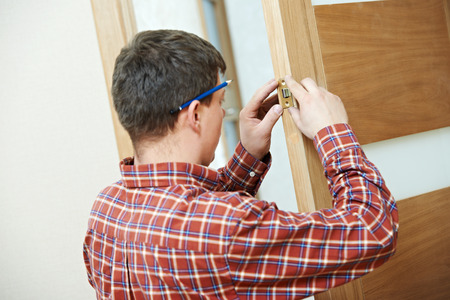 deadbolt: Male handyman carpenter at interior wood door lock installation
