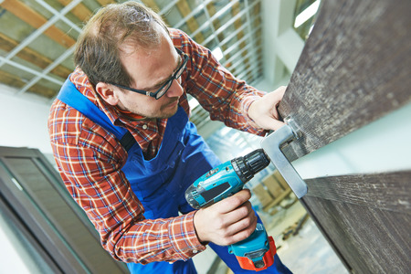 doorlock: carpenter at interior wood door lock installation working with drill Stock Photo