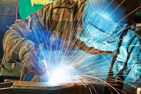 welder working with electrode at semi-automatic arc welding in manufacture production plant