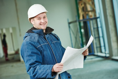 real leader: young male engeneer worker foreman at a indoors building site with blueprints