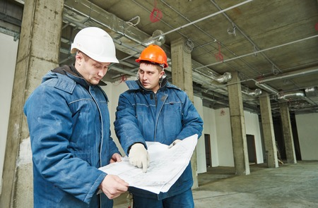 foremaster: young male engeneers workers foreman at a indoors building site with blueprints Stock Photo