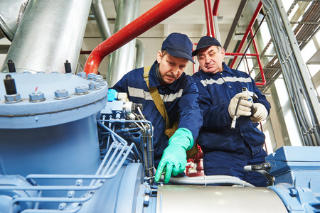 service engineer worker at industrial compressor refrigeration station repairing and adjusting equipment at manufacturing factory Standard-Bild