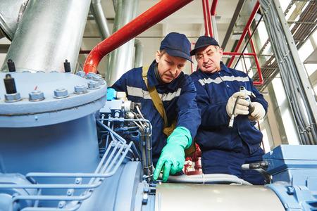 ingeniero: trabajador ingeniero de servicio al compresor industrial estaci�n de refrigeraci�n y reparaci�n de equipos de ajuste en f�brica de la fabricaci�n Foto de archivo