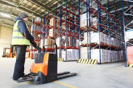warehousing: Electric forklift pallet stacker truck equipment at work in warehouse