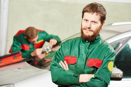 glasscutter: Automobile glazier repairman portrait in front of worker repairing car windscreen in auto service station garage Stock Photo