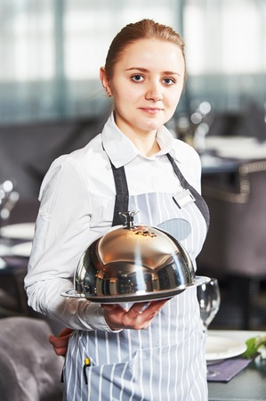 cloche: Waitress with tray and cloche at the indoor restaurant service Stock Photo