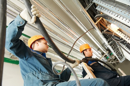 industrial industry: two electrician builder engineers workers installing industrial cable into fuse box