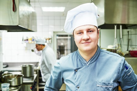 servicing: portrait of male cook chef at restaurant kitchen