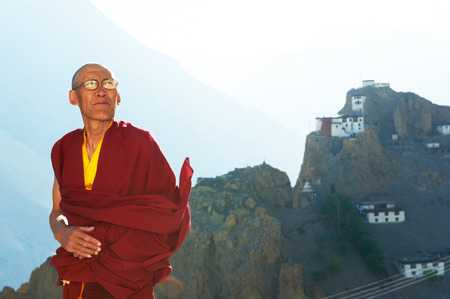 himalayas: Indian tibetan old monk lama in red color clothing in front of mountain with monastery Stock Photo
