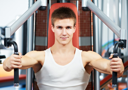 deltoid: smiling fitness man at chest pectoral muscles exercises with training weight machine station in gym