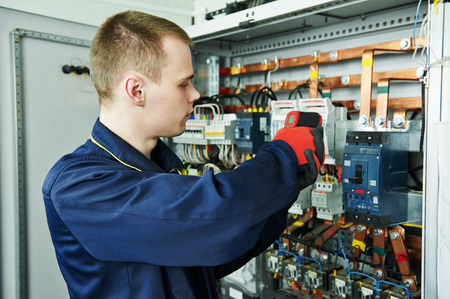 electrician inspector cheching power of fuseboard equipment in boiler room Archivio Fotografico