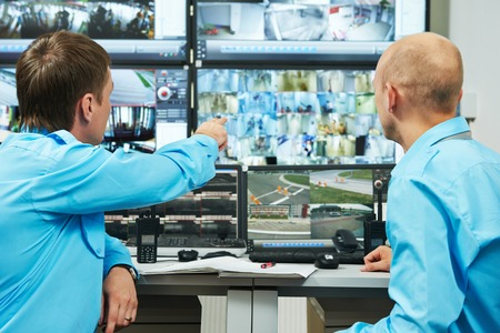 thief: security executive chief discussing activity with worker in front of video monitoring surveillance security system Stock Photo