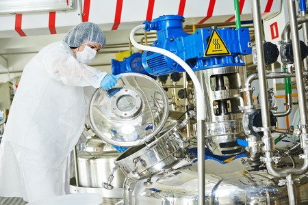 chemical plant: pharmaceutical worker with equipment mixing tank on production line in pharmacy industry manufacture factory Stock Photo