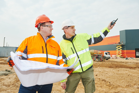 male engineers construction foreman managers outdoors at building site with blueprints Stock Photo