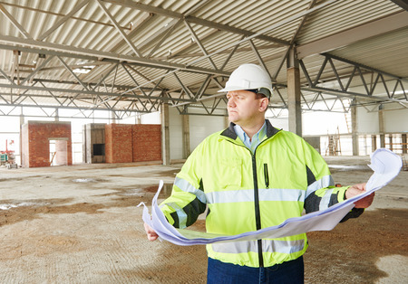 protection plan: construction engineer manager with blueprint drawing project plan at building site Stock Photo