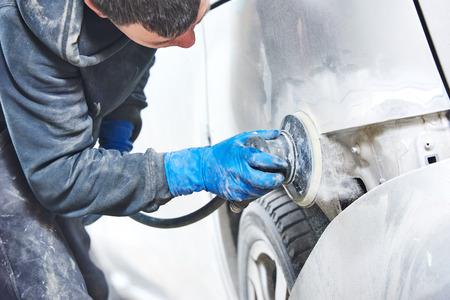 mechanik mechanik szlifowanie polerowanie pracownika samochodu i przygotowanie ciała do malowania samochodu podczas naprawy i odnowienia w sklepie stacji paliw