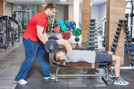 work out: fitness and sport concept. personal coach trainer helps man work out at a gym with heavy weight