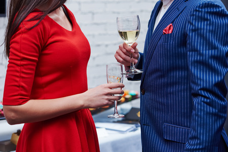 hospitality: Two guests of formal evening party celebration holding glasses of wine in their hands Stock Photo