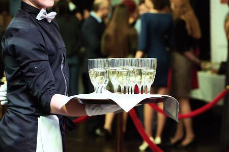 ケータリングやお祝いのコンセプトです。パーティーでつるのメガネでトレイを保持ウェイター