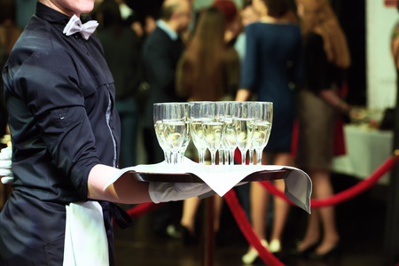 catering or celebration concept. Waiter holding a tray with glasses of vine at party Фото со стока