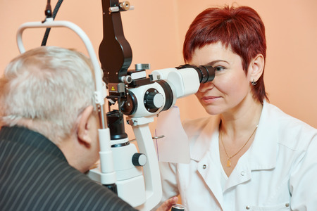 diopter: Optometry concept. female optometrist optician doctor examines eyesight of female patient in eye ophthalmological clinic Stock Photo