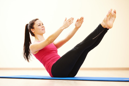 pilate: young female instructor doing stretching pilates exercises in sport club