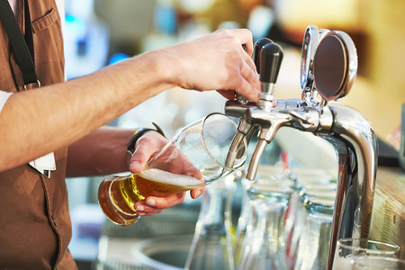barman hand at beer tap pouring a draught lager beer Archivio Fotografico