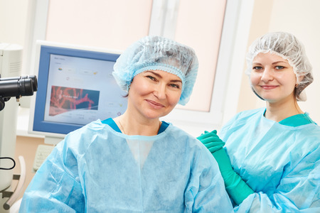 Female surgeon and assistant nurse portraits in uniform in eye vision surgery operation room at medical clinic photo