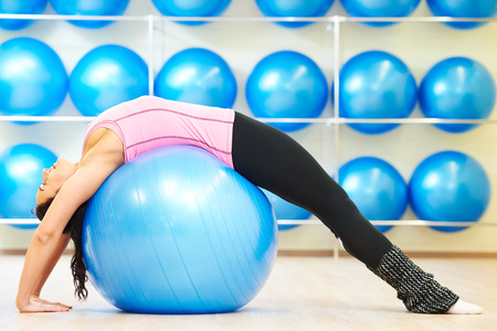 warm up exercise: woman doing stretching on fitness ball during pilates exercises in sport club