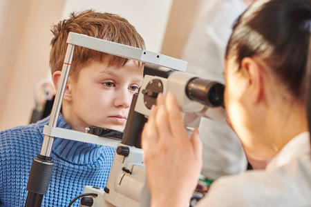 diopter: Child optometry. female optometrist optician doctor examines eyesight of little boy patient in eye ophthalmological clinic