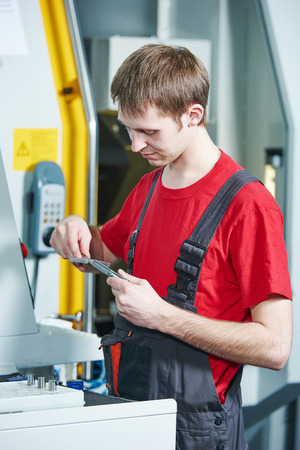 ncc: manufacture worker measuring detail at factory metal machining shop Stock Photo
