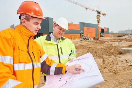 two engineers construction foreman managers at building site with blueprints