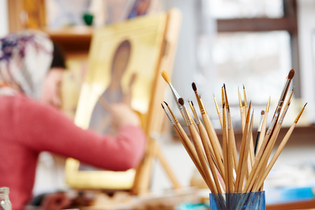 artist: Iconography. brushes heap with woman painting the Mother of God icon on background Stock Photo