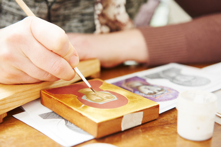 iconography: Iconography. woman painter hand with brush paints a new Mother of God icon at workshop