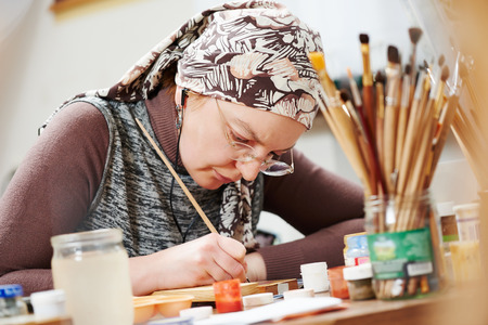 gilding: iconography. painter woman paints a new icon with brush at workshop