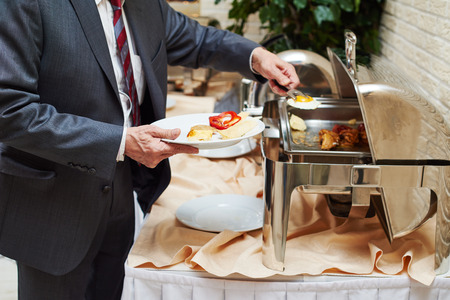 buffet lunch: restaurant catering service. Man with food at morning buffet style smorgasbord