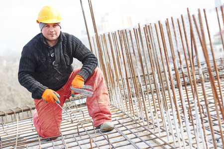 concrete construction: construction worker portrait during reinforcement work with metal rebar rods at building site
