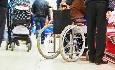 supermarkets: wheelchair bound invalid buyer in shopping center with assistant