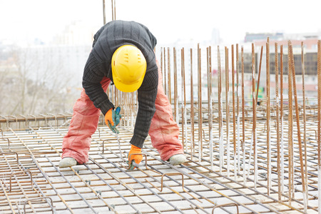 erector: construction worker making reinforcement with metal rebar rods at building site