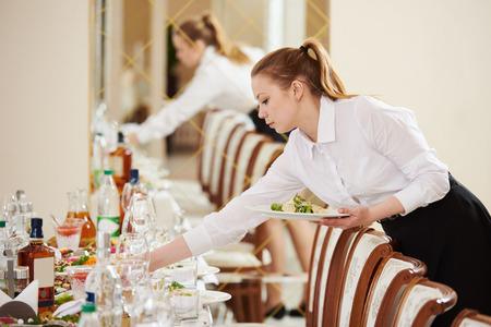 meseros: Servicios de catering del restaurante. camarera sirve mesa del banquete